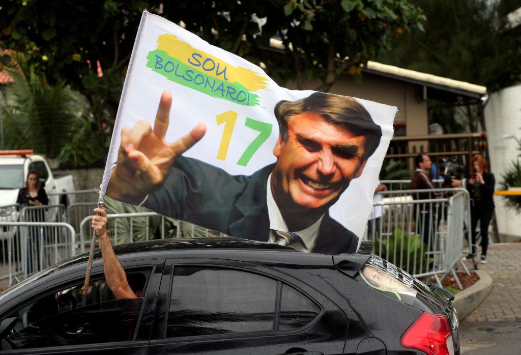 A supporter of Brazil's new president-elect, Jair Bolsonaro, celebrates in front of Bolsonaro's condominium at Barra da Tijuca neighborhood in Rio de Janeiro, Brazil. Photo by Sergio Moraes/Reuters