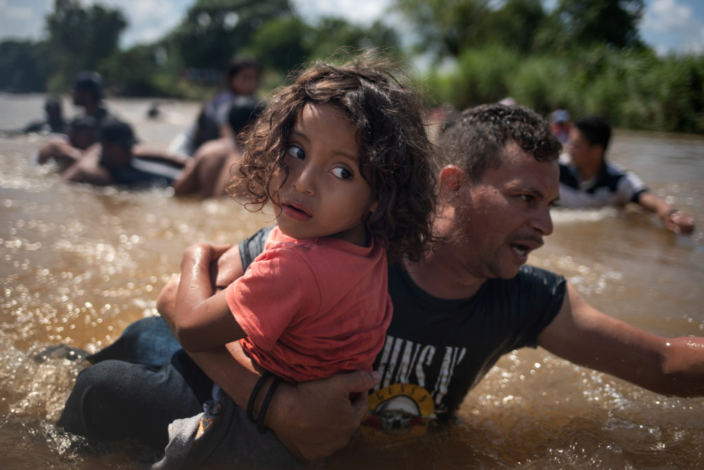 Luis Acosta holds 5-year-old Angel Jesus, both from Honduras, as a caravan of migrants from Central America en route to th...