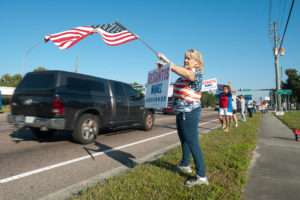 Kathleen Callahan wore a flag to wave a flag and a sign of her favorite candidate in New Port Richey, Florida. Photo by Jay Nolan for the PBS NewsHour.