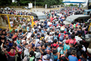 Honduran migrants, part of a caravan trying to reach the U.S., storm a border checkpoint to cross into Mexico, in Tecun Uman, Guatemala October 19, 2018. Photo by REUTERS/Ueslei Marcelino