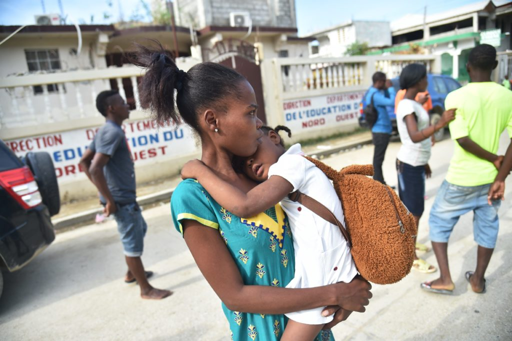 Haitians react during the aftershock of an earthquake in the city of Port-de-Paix, on October 7, 2018. - A 5.9-magnitude earthquake struck off the northwest coast of Haiti late Saturday, killing at least 12 people, injuring more than 130 others and damaging homes in the poverty-stricken Caribbean nation, authorities said. (Photo by HECTOR RETAMAL / AFP) (Photo credit should read HECTOR RETAMAL/AFP/Getty Images)