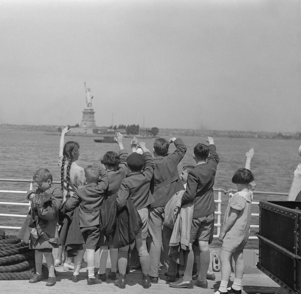 A group of young Austrian immigrants wave to the Statue of Liberty upon their arrival in America aboard the S.S. Harding. The fifty Jewish children, who were greeted by their new adoptive families, were fleeing Nazi persecution in their homeland. Photo by Bettmann/via Getty Images