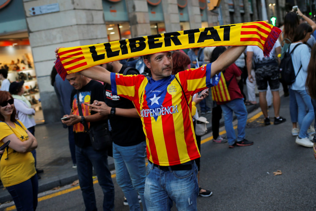 """A demonstrator holds up a banner reading """"Freedom""""  during a demonstration on the first anniversary of Catalonia's October 1, 2017 banned referendum on independence in Barcelona, Spain, October 1, 2018. REUTERS/Jon Nazca"""