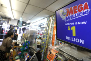 A sign displays the jackpot for Mega Millions as customers buy lottery tickets in midtown Manhattan in New York, U.S., October 19, 2018. Photo by REUTERS/Mike Sugar