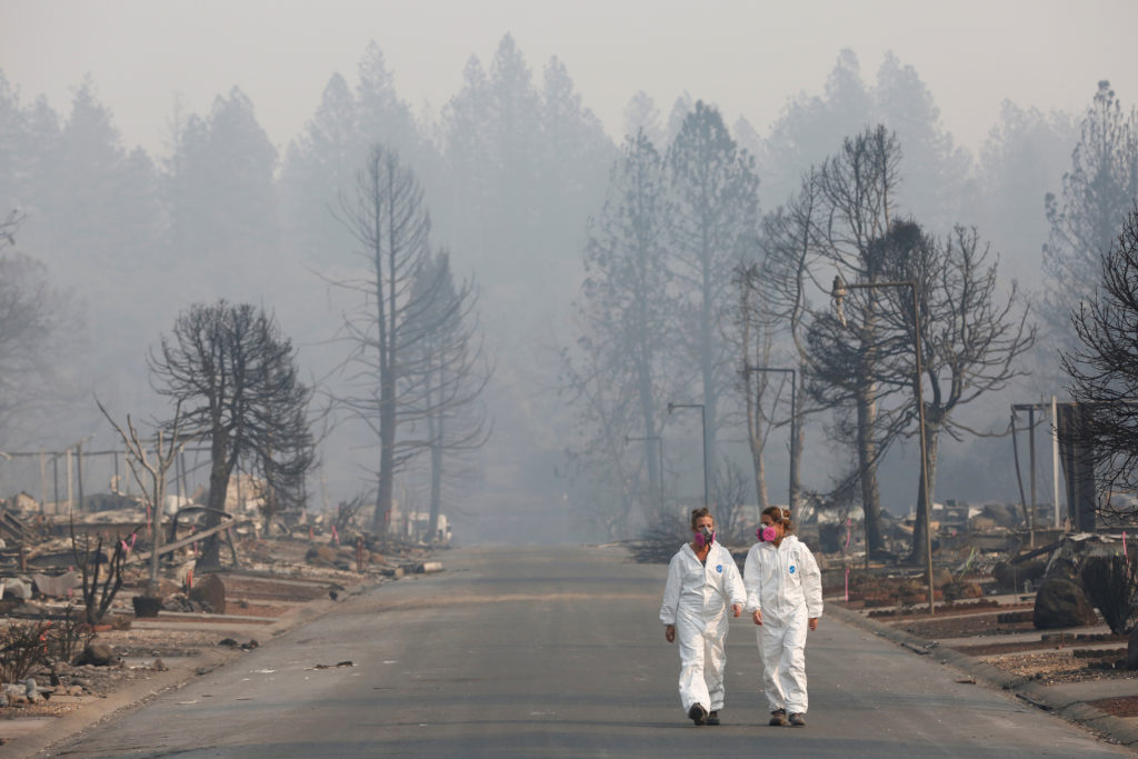 Forensic anthropologists Kyra Stull (L) and Tatiana Vlemincq walk through a trailer park destroyed by the Camp Fire in Paradise, California, U.S., November 17, 2018. REUTERS/Terray Sylvester