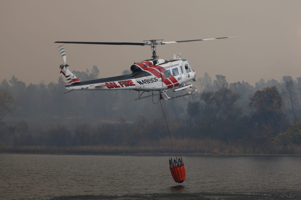 A Cal Fire helicopter picks up water from a reservoir while battling the Camp Fire in Paradise, California, U.S. November 8, 2018. Photo by REUTERS/Stephen Lam