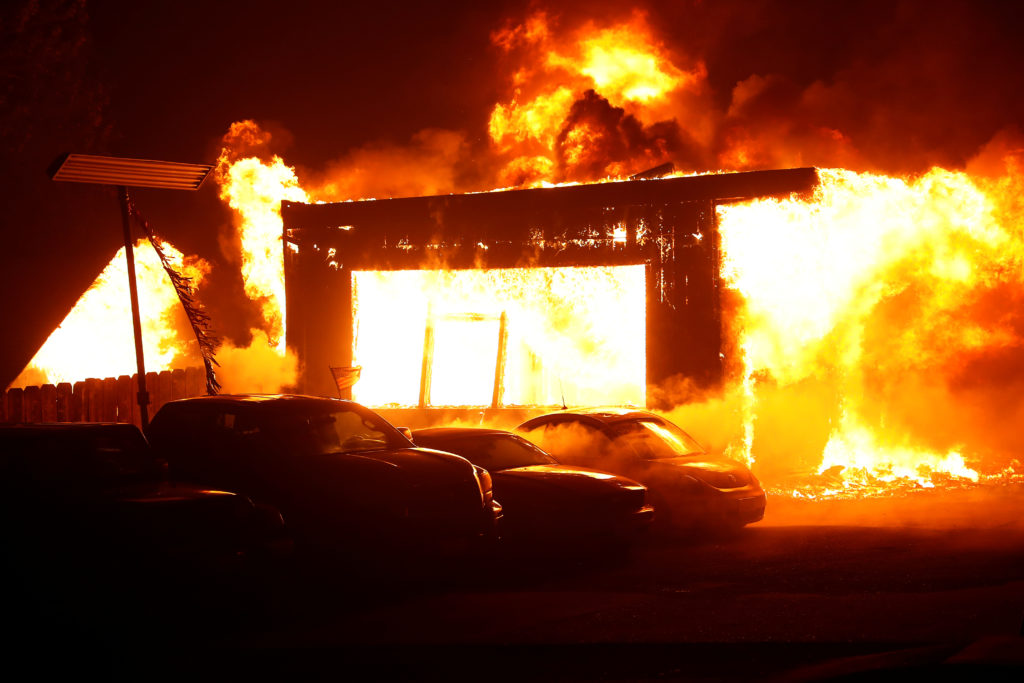 An used car dealership is seen engulfed in flames during the Camp Fire in Paradise, California, U.S. November 8, 2018. Photo by REUTERS/Stephen Lam