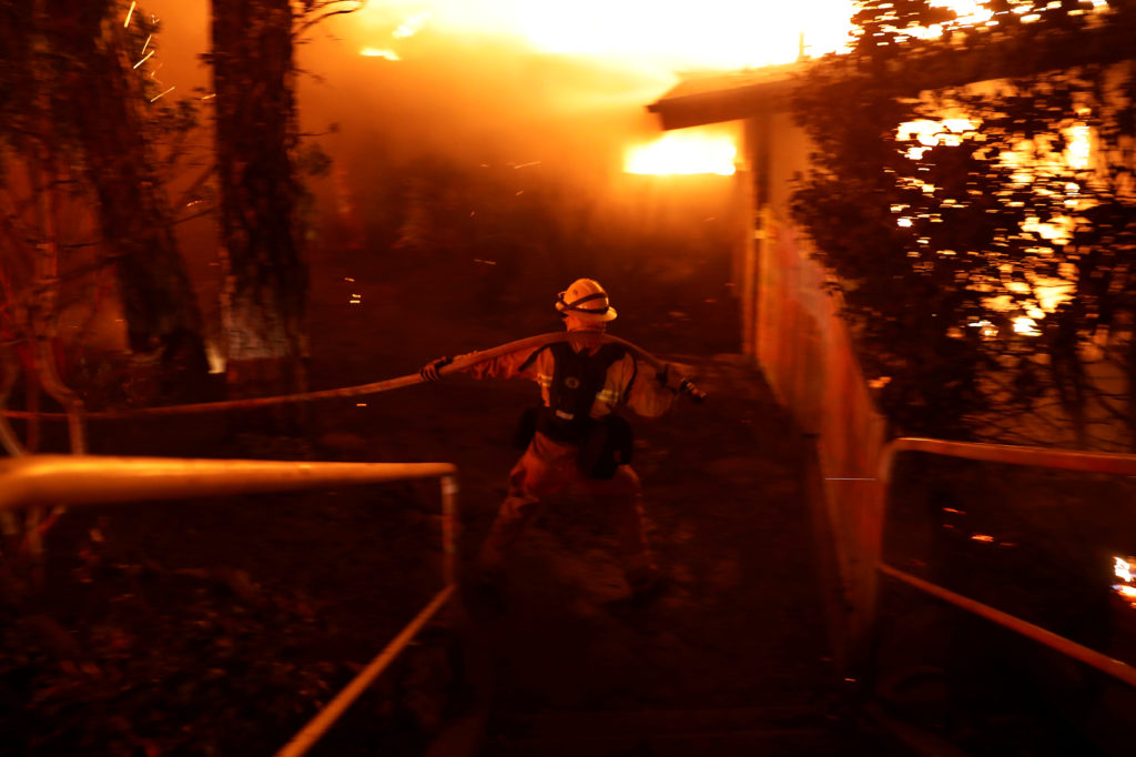 A firefighter drags a hose as he battles the Camp Fire in Paradise, California, U.S. November 8, 2018. Photo by REUTERS/Stephen Lam