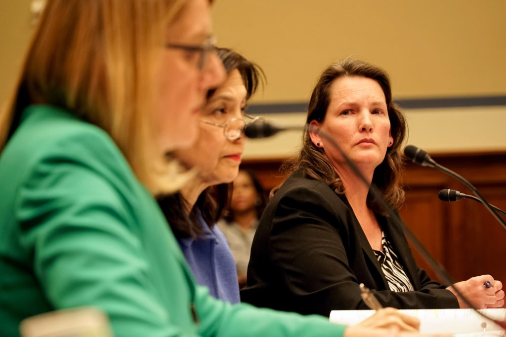 Former U.S. Forest Service employee Shannon Reed listens as the agency's chief Vicki Christiansen testifies before a House committee hearing Thursday. Photo by William Brangham/PBS NewsHour