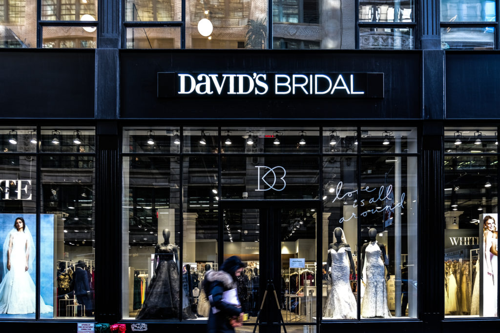 A pedestrian passes in front of a David's Bridal Inc. store in New York. David's Bridal Inc. is filing for bankruptcy protection. Photo by Jeenah Moon/Bloomberg via Getty Images