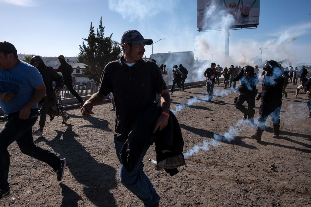 Central American migrants run along the Tijuana River near the border crossing in Tijuana, Mexico, after the U.S. Border Patrol threw tear gas to disperse the crowd attempting to cross into the U.S. Photo by Guillermo Arias/AFP/Getty Images