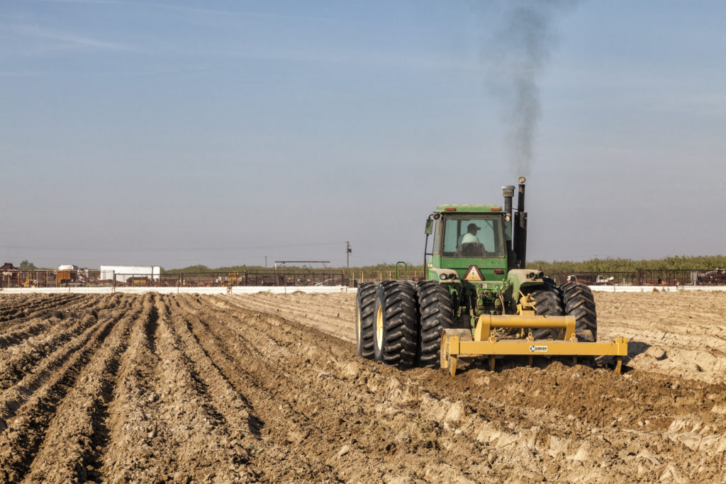 Tractor hoeing crop field for planting. Fresno County, San Joaquin Valley, California. (Photo by: Citizens of the Planet/E...