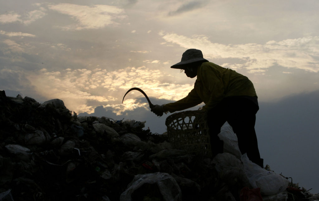A Thai rag-picker searches for plastic waste at a garbage dump site in Thailand's Ayutthaya province, about 50 miles north of Bangkok. Much of Southeast Asia's waste management is done by the informal workforce who make money from the recyclables they collect. Photo by Sukree Sukplang/Reuters