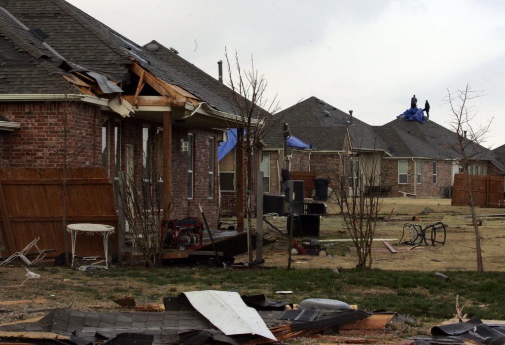 Workers can be seen in the distance as they cover the roof of a damaged home after a suspected tornado and heavy storms hit Edmond, Oklahoma in 2008. Insurers offer some discounts to homeowners who refit their homes to withstand tornado damage or other natural disasters. Photo by Mike Stone/Reuters