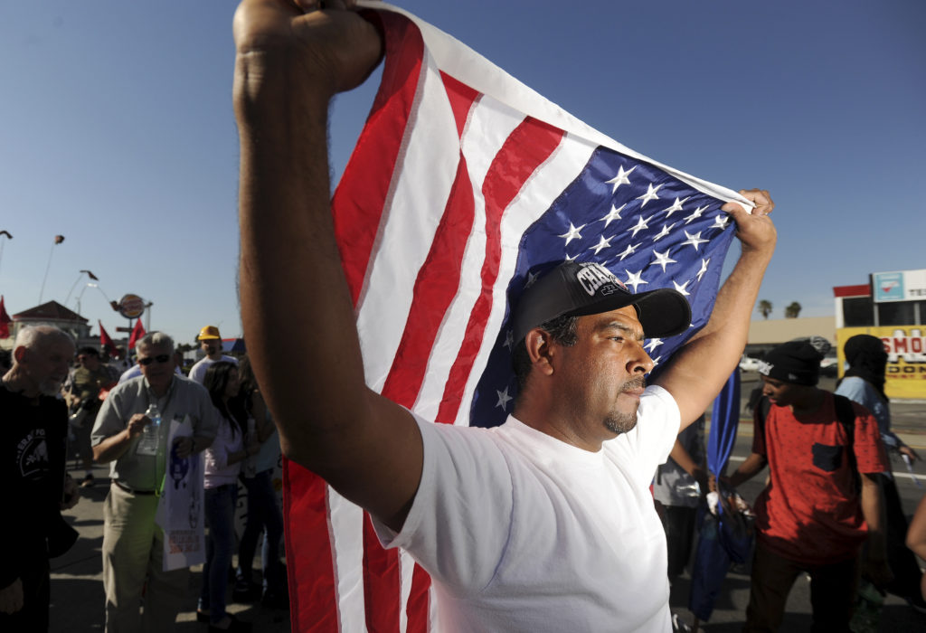 Oscar Rojas carries an American flag during demonstration calling for immigration reform in Oakland, California. Photo by ...
