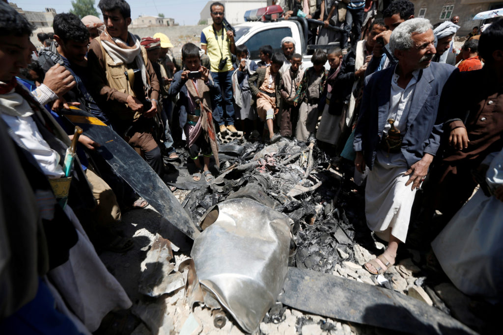 People gather around the engine of a drone aircraft which the Houthi rebels said they have downed in Sanaa, Yemen, on Oct....