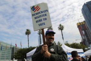 A Democratic Party worker holds up a sign encouraging immigrants who have become new U.S. citizens to sign up to vote in the upcoming midterm elections outside a naturalization ceremony in Los Angeles, California. Photo by Lucy Nicholson/Reuters