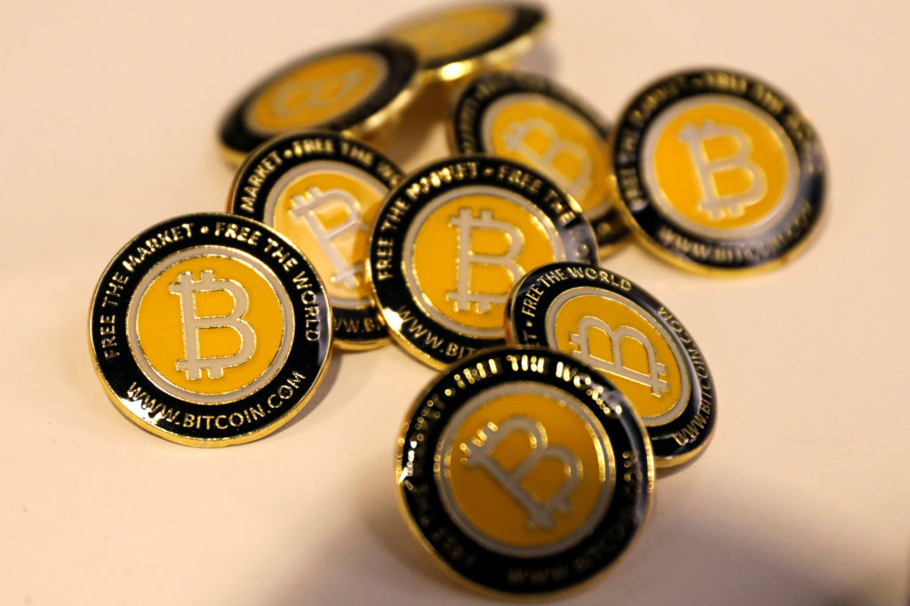 Bitcoin.com buttons are seen displayed on the floor of the Consensus 2018 blockchain technology conference in New York City. Bitcoin has lost about 40 percent of its value in the last month. iPhoto by Mike Segar/Reuters