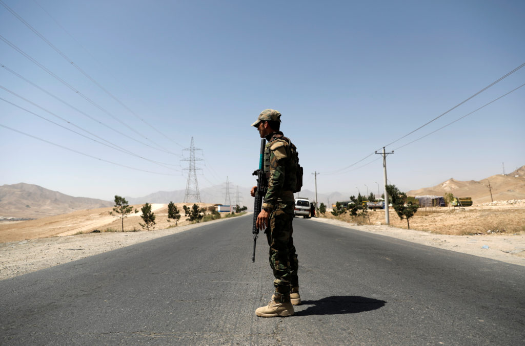 An Afghan National Army (ANA) soldier keeps watch at a checkpoint on the Ghazni highway, in Maidan Shar, the capital of Wa...