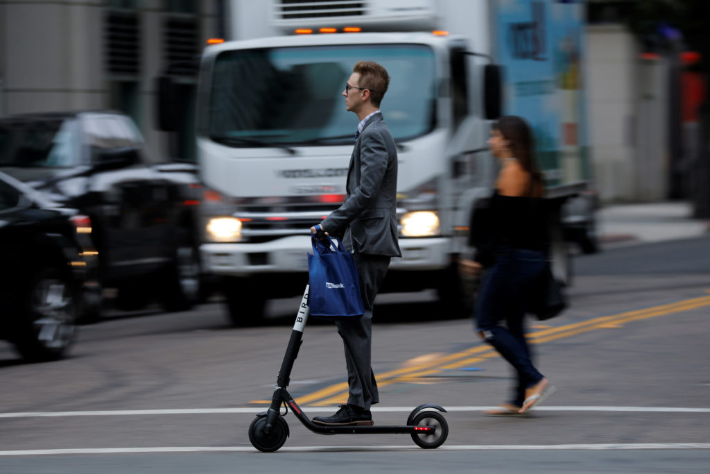 A man rides an electric Bird scooter along a city street in San Diego, California. Bird is valued at $2 billion. Photo by Mike Blake/Reuters