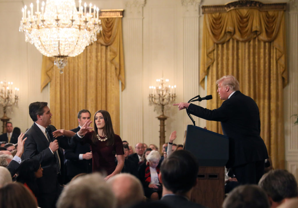 A White House staff member reaches for the microphone held by CNN's Jim Acosta as he questions President Donald Trump duri...