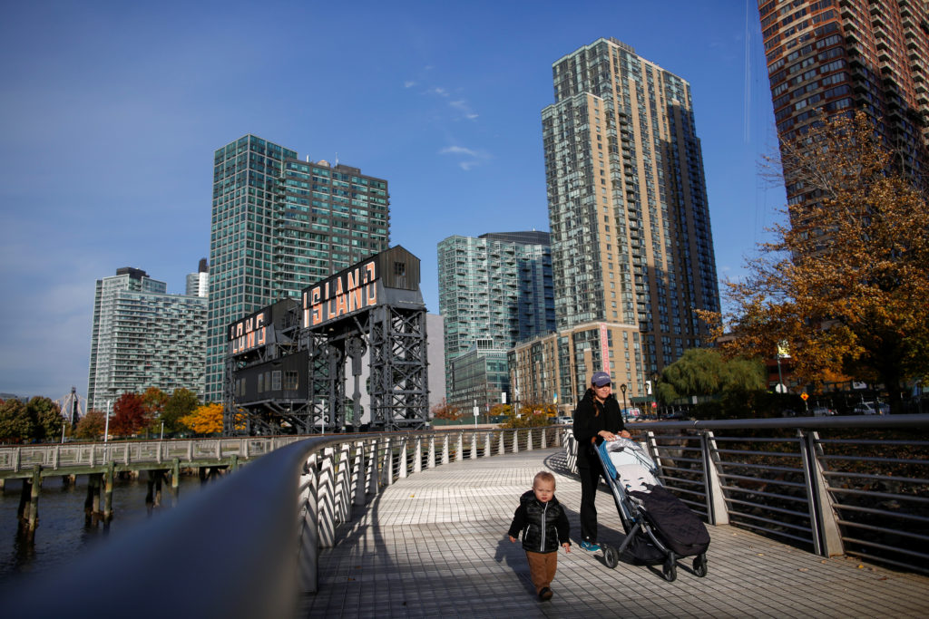 People walk along Gantry Plaza State Park, in Long Island City, where Amazon.com is reportedly considering as part of its new second headquarters. Photo by Eduardo Munoz/Reuters