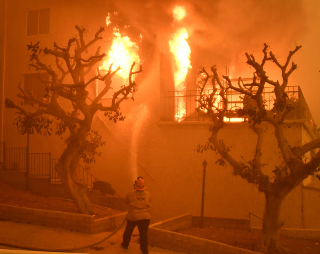A firefighter hoses down a condo unit during the Woolsey Fire in Ma…