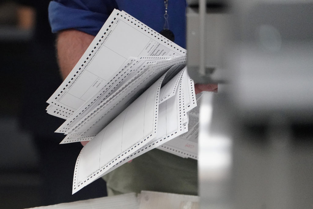 A worker holds ballots before a ballot recount in Lauderhill, Florida. Photo by Carlo Allegri/Reuters