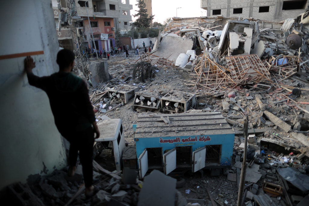 A Palestinian man looks at the remains of Hamas's TV station building that was destroyed by Israeli air strikes, in Gaza C...
