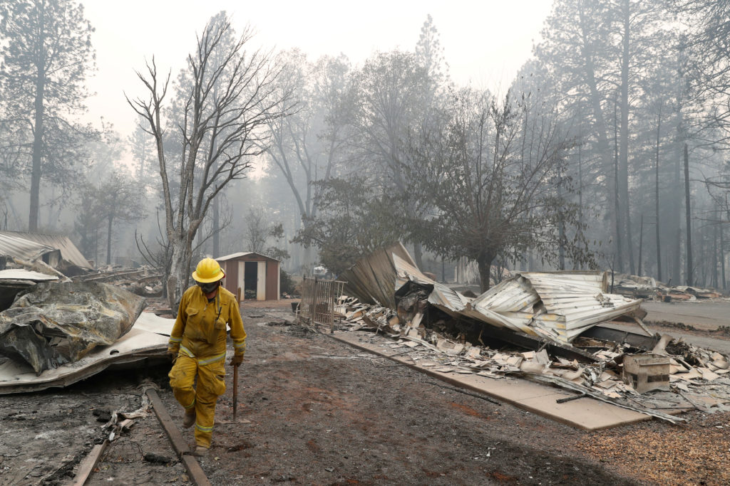 A Cal Fire firefighter walks between homes destroyed by the Camp Fire in Paradise, California. Residents say the evacuation orders came so fast, many had to leave everything beyond. Photo by Terray Sylvester/Reuters