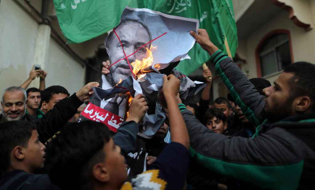 Palestinians burn a poster depicting Israel's Defence Minister Avigdor Lieberman as they celebrate after Lieberman announced his resignation, in Gaza City. Photo by Suhaib Salem/Reuters