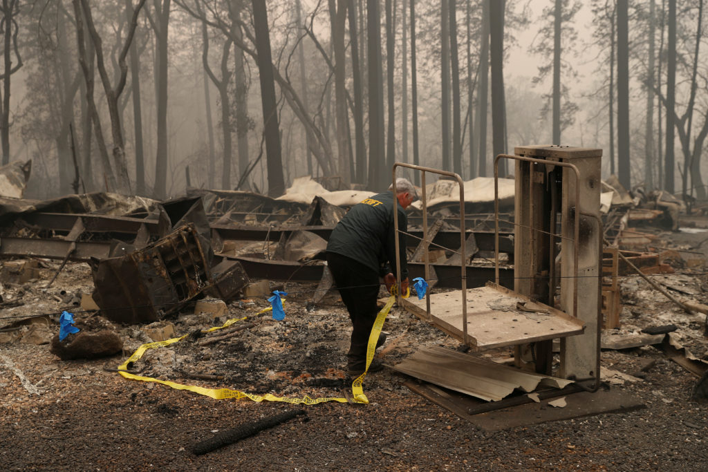 A Butte County Sheriff deputy places yellow tape at the scene where human remains were found during the Camp fire in Paradise, California, U.S. November 10, 2018. Photo by Stephen Lam/Reuters