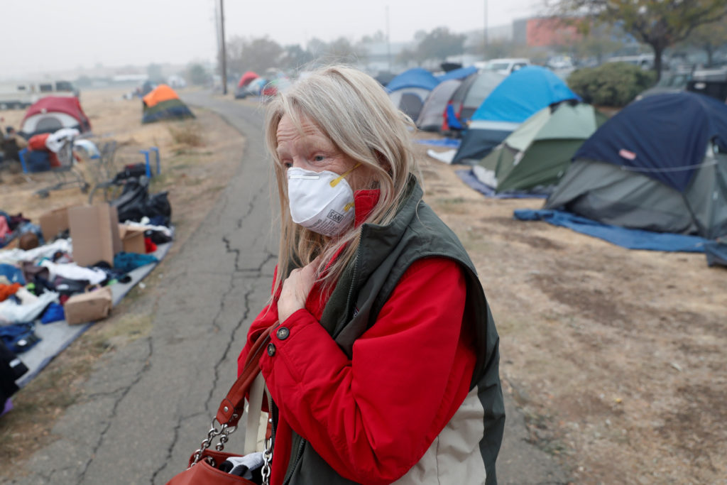 Bridgett Hogan, 57, of Paradise, walks through a makeshift evacuation center for people displaced by the Camp Fire in Chico, California, U.S., November 15, 2018.  Photo by Terray Sylvester/Reuters