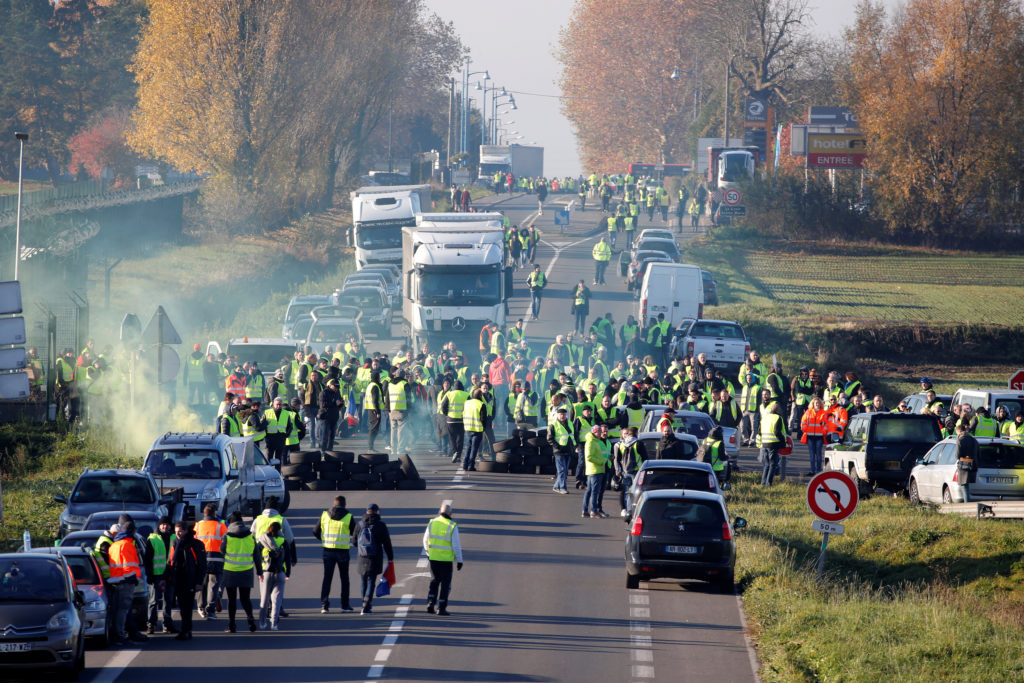 People wearing yellow vests a symbol of a French drivers&#039 nationwide protest against higher fuel prices block the Paris Brussels motorway in Haulchin France