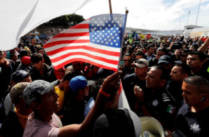 A migrant, part of a caravan of thousands traveling from Central America en route to the United States, holds a U.S. flag as the group of migrants negotiate with Mexican policemen during their gathering near the El Chaparral port of entry of border crossing between Mexico and the United States in Tijuana, Mexico November 22, 2018. Photo by Kim Kyung-Hoon/Reuters