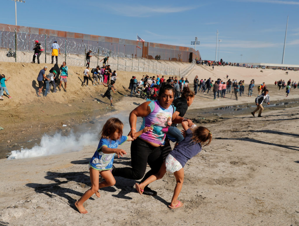 A migrant family, part of a caravan of thousands traveling from Central America en route to the United States, run away from tear gas in front of the border wall between the U.S and Mexico in Tijuana, Mexico November 25, 2018. Photo by Kim Kyung/Reuters