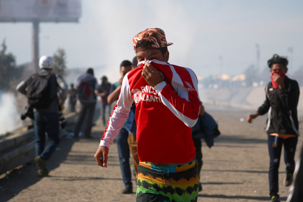 A migrant covers his face as he runs from tear gas, thrown by the U.S border patrol, near the fence between Mexico and the United States in Tijuana, Mexico, November 25, 2018. Photo by Hannah McKay/Reuters