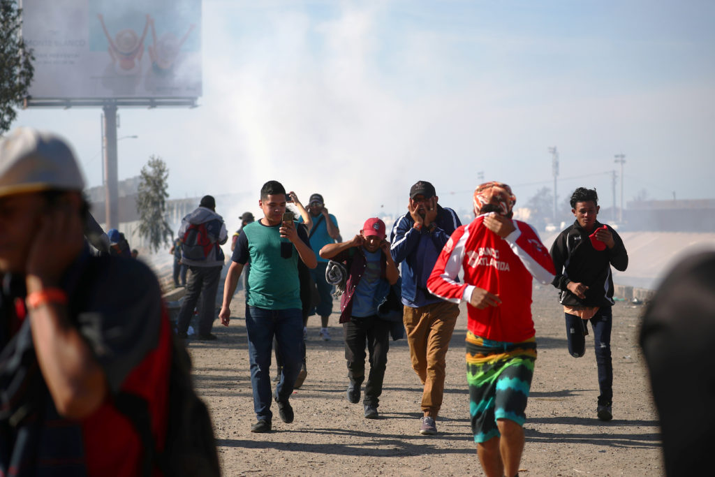 Migrants cover their faces, as they run from tear gas, thrown by the U.S border patrol near the fence between Mexico and the United States in Tijuana, Mexico. Photo by Hannah McKay/Reuters