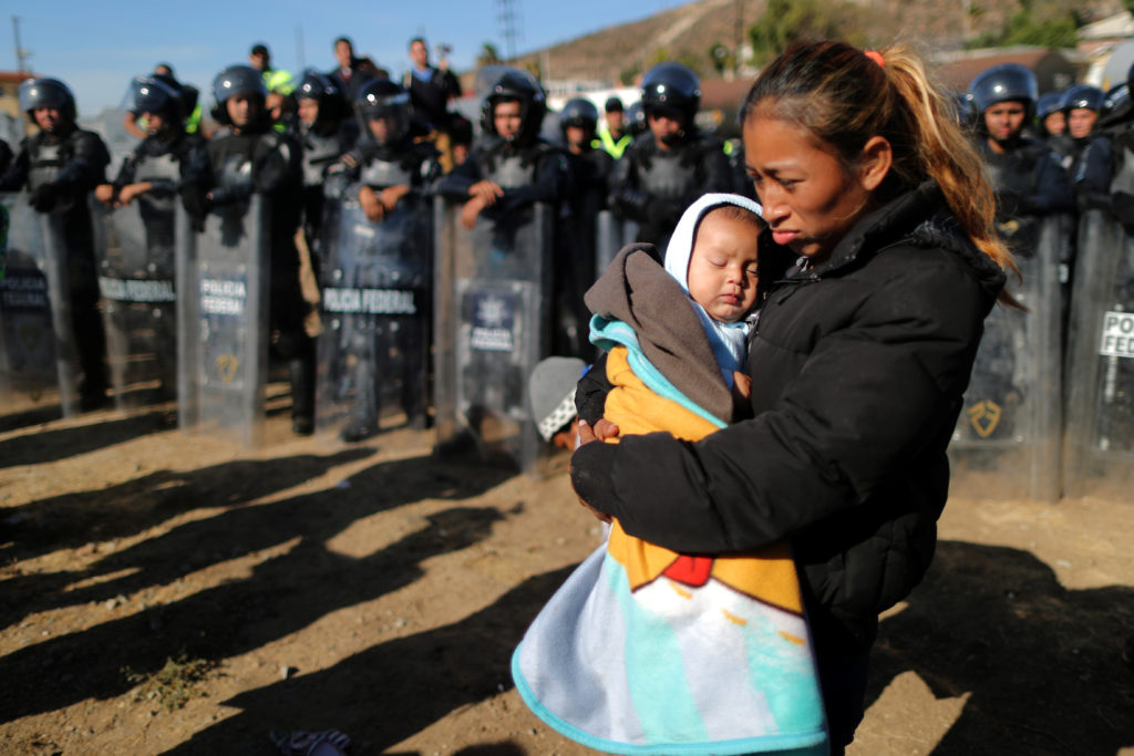Rosa Villa, 30, and her five-month-old son Esteban from Honduras, part of a caravan of thousands traveling from Central America en route to the United States, are pushed back from the border wall between the U.S and Mexico by Mexican police in Tijuana, Mexico. Photo by Lucy Nicholson/Reuters