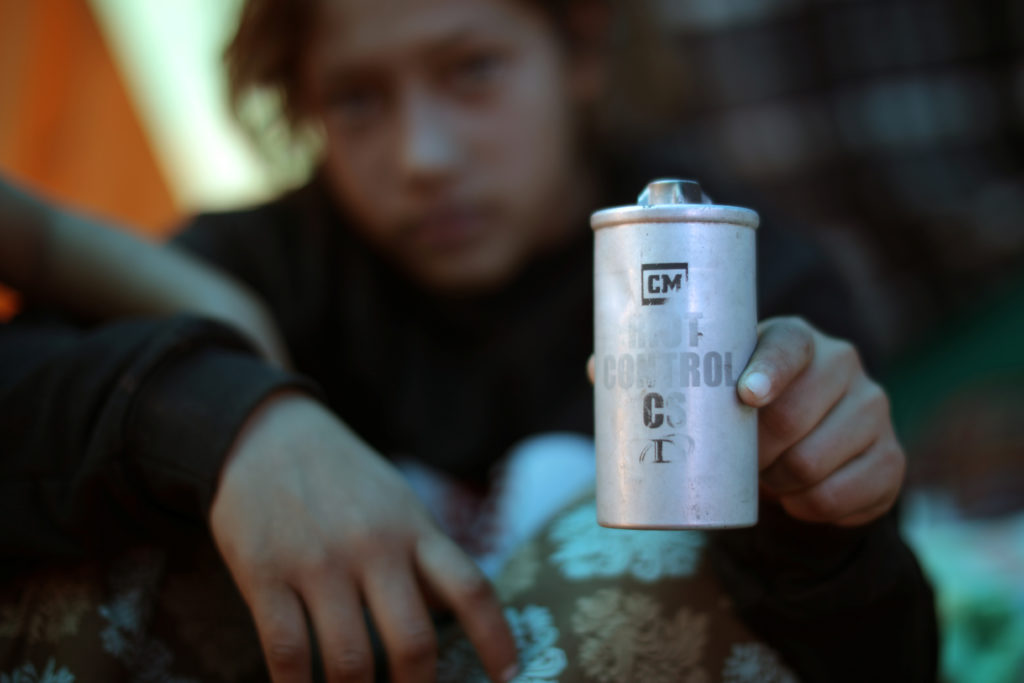 Jamie Jisel Mejia Meza, 13, from Honduras, who is part of a caravan of thousands from Central America trying to reach the United States, holds a tear gas canister she picked up as she sits in a temporary shelter in Tijuana, Mexico. Photo by Lucy Nicholson/Reuters