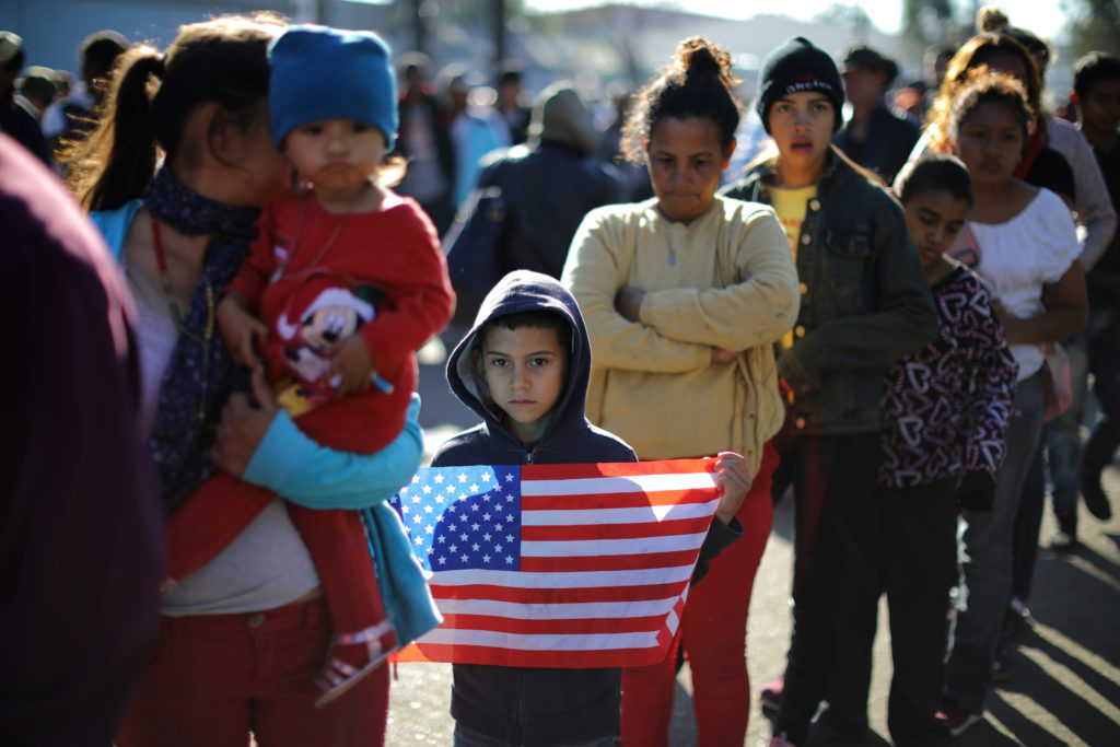 Marie Orellana, 28, (4th L) and her seven-year-old son Angel (3rd L holding flag), from Honduras, part of a caravan of thousands of migrants from Central America trying to reach the United States, queue for food outside a temporary shelter in Tijuana, Mexico, November 25, 2018. Picture taken November 25, 2018. REUTERS/Lucy Nicholson - RC1B61A7F8F0