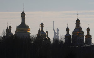 Domes of the Dormition Cathedral of the Kiev Pechersk Lavra monastery are seen in front of the Mother Homeland monument in Kiev, Ukraine November 30, 2018. REUTERS/Valentyn Ogirenko