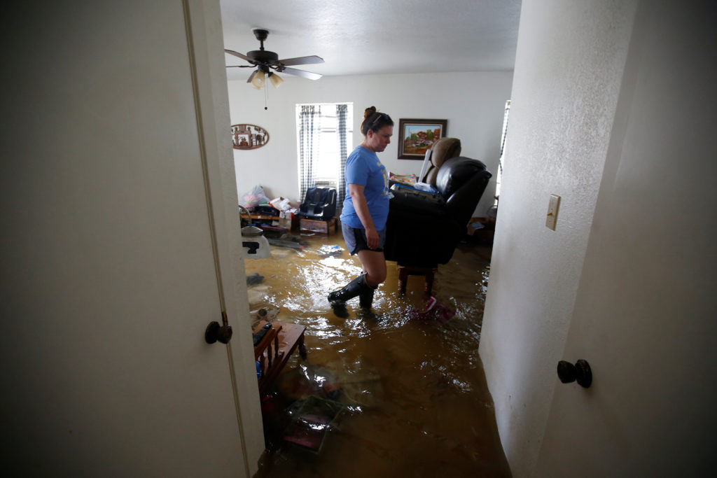 A woman wades though a flooded living room of a house on a farm after Tropical Storm Harvey in Orange, Texas on September 1, 2017. The National Flood Insurance Program paid out more than $8 billion in claims after the storm. Photo by Carlo Allegri/Reuters