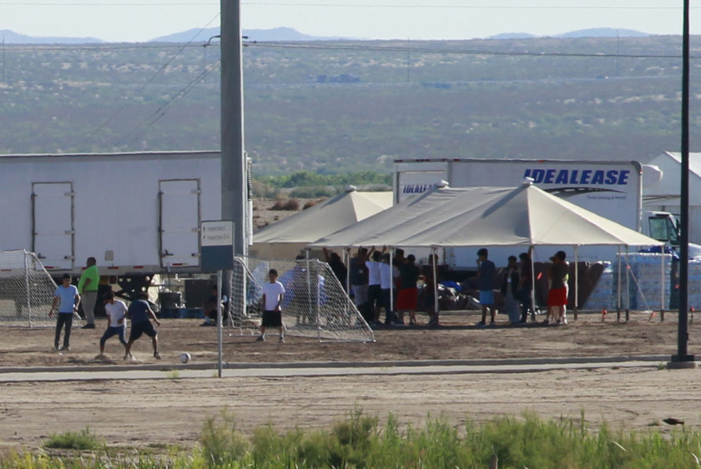 Children of detained migrants play soccer at a newly constructed tent encampment as seen through a border fence near the U.S. Customs and Border Protection (CBP) port of entry in Tornillo, Texas. Photo taken in June. Photo by Jose Luis Gonzalez/Reuters