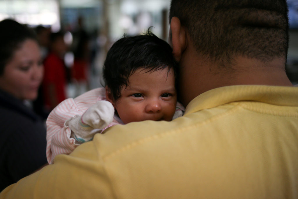 An undocumented immigrant father from Honduras and his infant daughter are released from detention with other families at a bus depot in McAllen, Texas. A study of immigration in Germany found children given citizenship at birth had better health outcomes. Photo by Loren Elliott/Reuters