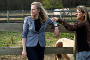 Virginia Democratic candidate for U.S. Representative Abigail Spanberger (L) talks with Jorg Huckabee-Mayfield during a visit to the horse rescue stables she and her husband operate in Burkeville, Virginia, U.S. October 31, 2018. REUTERS/Jonathan Ernst - RC15A123A670