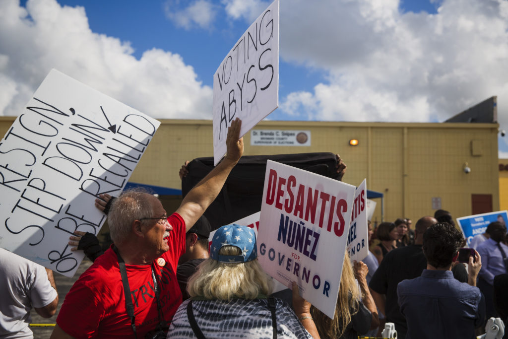 Republican protesters wave signs at the Broward County Supervisor of Elections office in Lauderhill, Fla. on Wednesday, November 14. Photo by Scott McIntyre for PBS New Hour
