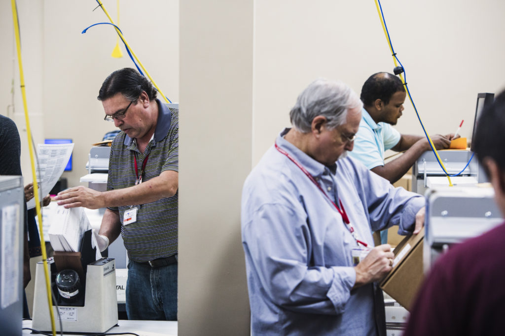 Voting technicians work in the ballot room at the Broward County Supervisor of Elections office in Lauderhill, FL on Wedne...