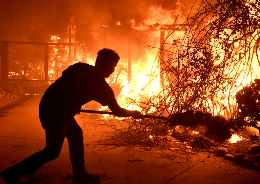 Home owner Will Buckley uses a shovel with dirt to try to stop the flames from from destroying a neighbor's home during the Woolsey Fire in Malibu, California, U.S. November 9, 2018. Photo by REUTERS/Gene Blevins