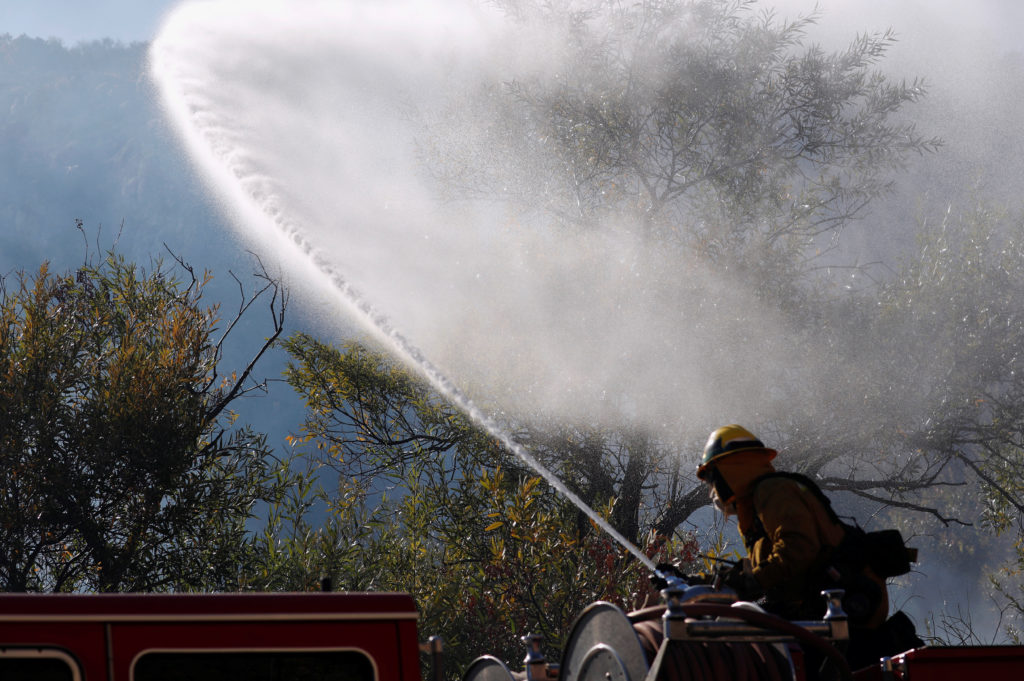 Firefighter sprays water from a hose as smoke is seen, while they battle the Woolsey fire in West Hills, Southern California, U.S. November 11, 2018. REUTERS/Mario Anzuoni
